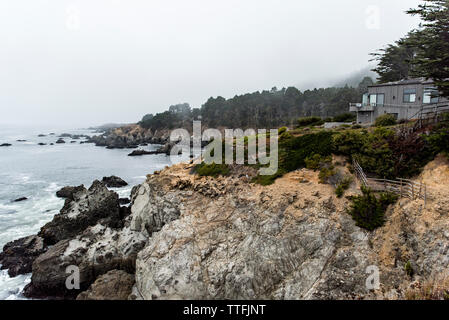 Coastal homes situated on rocky pacific headlands in the fog - Stock Photo