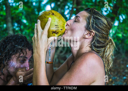 Side view of couple drinking from fresh coconut in forest - Stock Photo