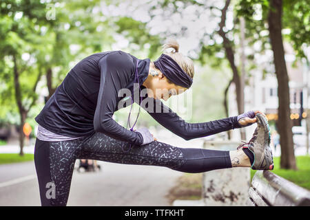 Athletic female stretching leg during daily workout - Stock Photo