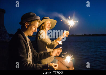 Young millennials with sparklers on road trip celebrating - Stock Photo