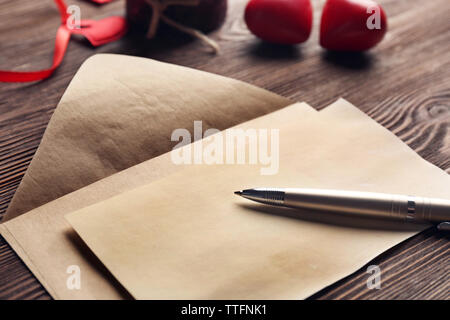 Gift card for Valentine's Day with pen and envelope on wooden background - Stock Photo
