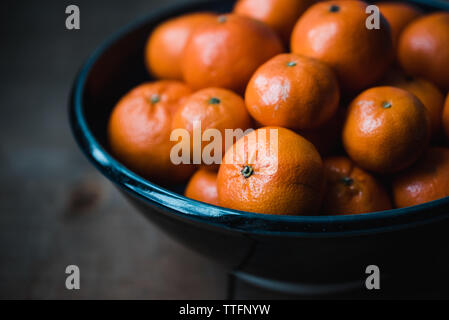 Close up of a bowl of fresh mandarin oranges in low light. - Stock Photo