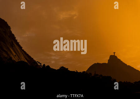 Beautiful orange sunset with mountains and Christ the Redeemer - Stock Photo