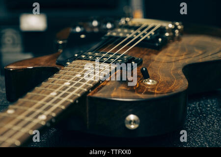 Close-up of guitar on table in studio - Stock Photo