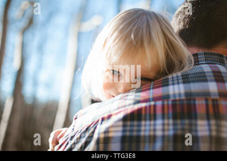 Father holding daughter, looking over his shoulder