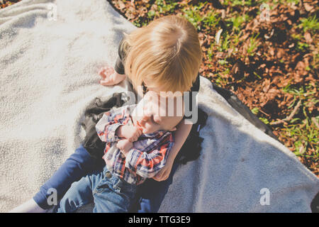 Sister holds her brother while on picnic blanket outside at park