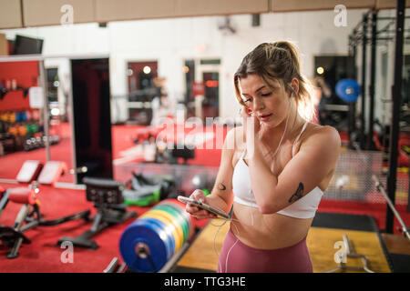 Young woman listening to music with earphones and smartphone at gym - Stock Photo