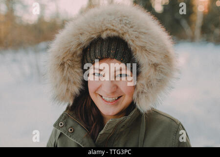 Portrait of an attractive young woman wearing a winter jacket. - Stock Photo