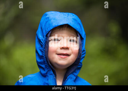 Portrait of little boy wearing hooded jacket in rain - Stock Photo