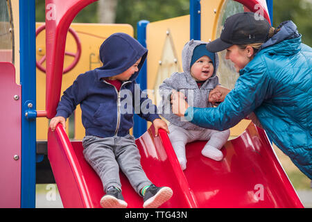 Mother and daughter on playground slide with older brother - Stock Photo