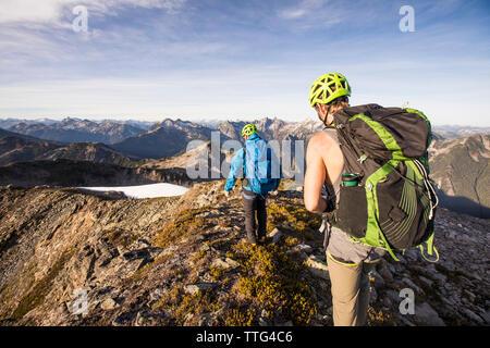 Backpackers hiking along mountain ridge, B.C. - Stock Photo