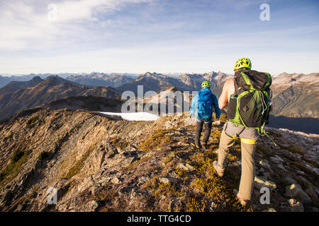 Backpackers hiking along high mountain ridge, B.C. - Stock Photo