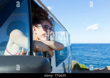 Happy woman looking through window while sitting in motor home - Stock Photo