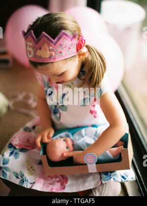 A five year old girl opens her birthday present - Stock Photo