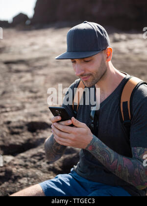 Young adult man using smartphone while sitting on rocks of the coast - Stock Photo