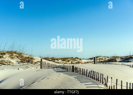 Drifting dunes with two sand fences, one with shadows, under blue sky - Stock Photo