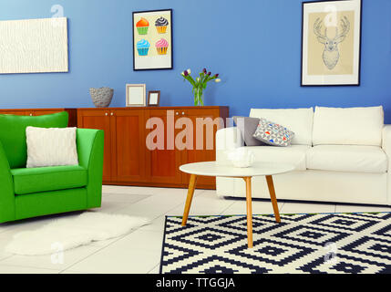 Modern living room interior with white sofa, coffee table, big graphic carpet, green chair and canvases on the blue wall - Stock Photo