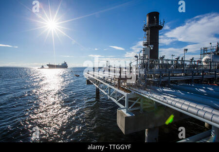 Factory by sea against blue sky - Stock Photo