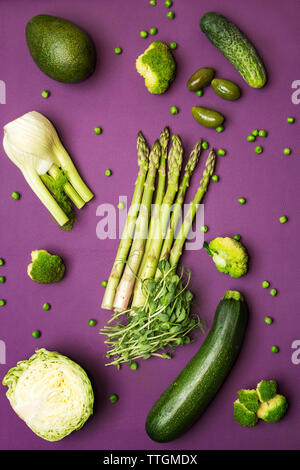 Overhead view of fresh green vegetables on purple table - Stock Photo