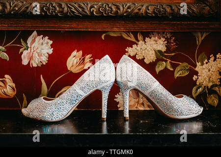 Brides shoes sitting on a black marble mantle with red wallpaper - Stock Photo