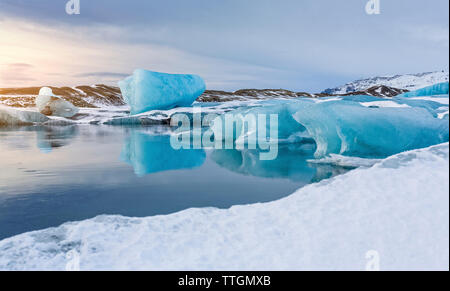 Scenic view of icebergs in lake against sky during winter - Stock Photo