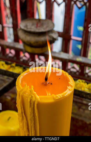 Candle in a temple in Thailand - Stock Photo