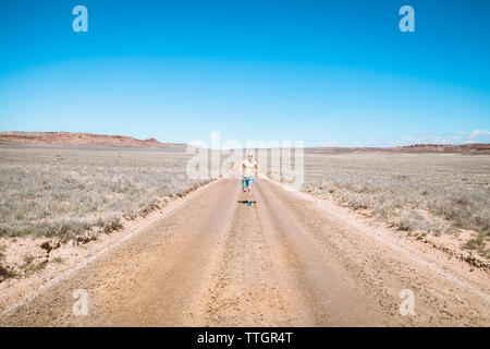 Mid distance of man running on dirt road amidst landscape against clear blue sky - Stock Photo