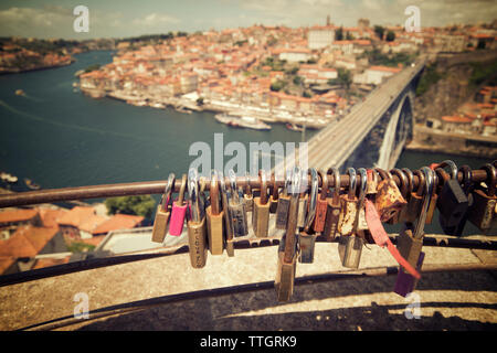 High angle view of padlocks on railing against cityscape - Stock Photo