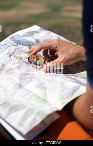 Cropped hands of hiker holding navigational compass with map - Stock Photo