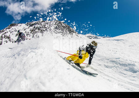 A man skis a banked course in the terrain park at Whistler Blackcomb. - Stock Photo