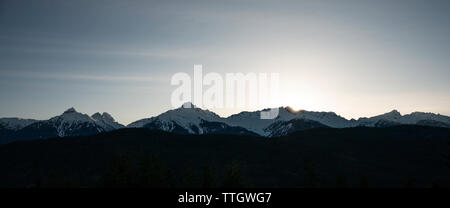 The sun sets behind the Tantalus Range beside the Sea to Sky Highway. - Stock Photo