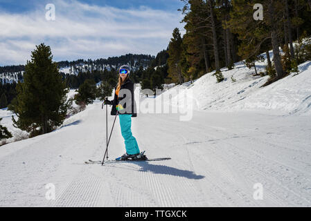 Woman skiing on snow covered field against sky in forest - Stock Photo