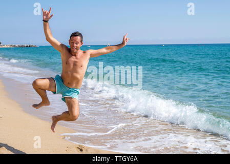 Front view of man in swimsuit jumping on seashore at beach sunny day - Stock Photo