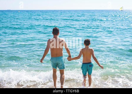 Rear view of father and son in swimsuite holding hands on seashore - Stock Photo
