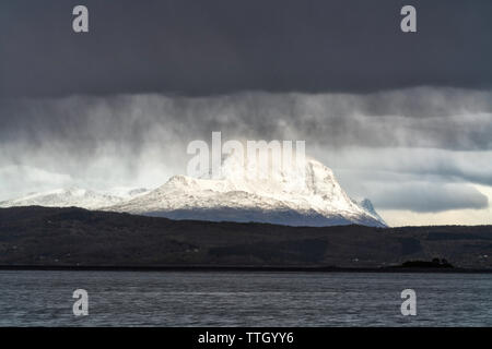 Storm clouds on snowy peaks and sea along Ofotfjord, Norway - Stock Photo