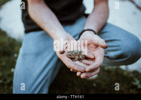 Close-up of man holding a toad - Stock Photo