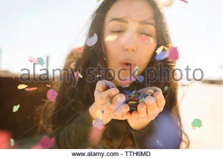 A Young long hair Woman Blowing colorful Confetti Stock Photo