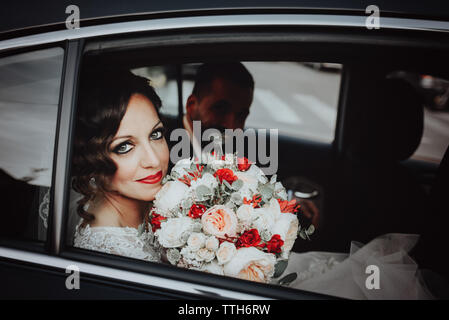 Dark-haired bride sits in a black car on your wedding day with a bouquet. - Stock Photo