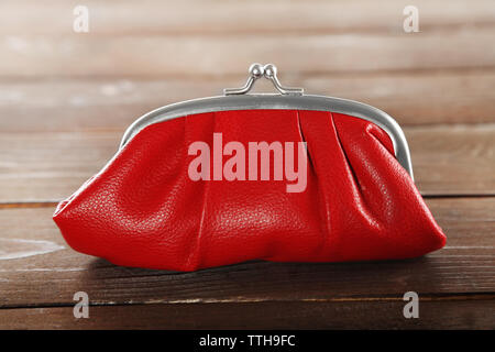Red leather purse on wooden background - Stock Photo