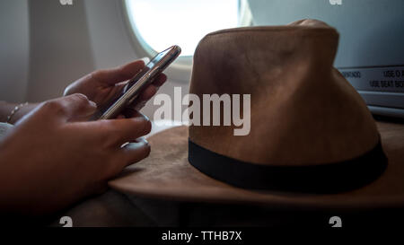 Young asian woman interior airplane. A passenger wear a hat on a plane using device phone during flight. Girl check the smartphone. Traveller sit down - Stock Photo