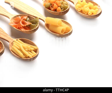 Different types of dry pasta in wooden spoons on white background - Stock Photo