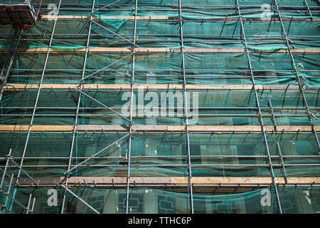 Professional scaffolding on the side of a building under renovation. - Stock Photo