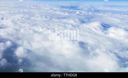 The beautiful cloudscape with clear blue sky. Panorama above white clouds as seen through window of an aircraft. A view from airplane - Stock Photo