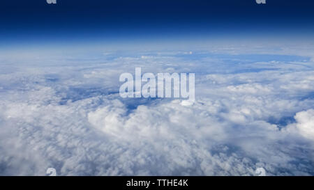 The beautiful cloudscape with clear blue sky. Panorama above white clouds as seen through window of an aircraft. A view from airplane. - Stock Photo