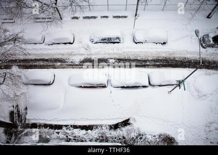 Overhead view of snow covered cars parked on city street - Stock Photo