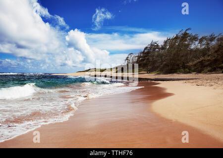 Idyllic view of sea waves rushing towards shore at beach against sky - Stock Photo