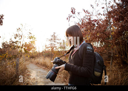 Woman looking at photographs on digital camera while standing on footpath - Stock Photo
