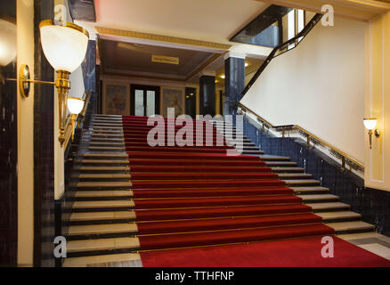 Main staircase in the Hotel International in Dejvice district in Prague, Czech Republic. The hotel inspired by Soviet Stalinist architecture was designed by Czech architect František Jeřábek and built in 1952-1956. The staircase railing was designed and manufactured by Czech artist Jan Nušl. According to the local legend, Czechoslovak army generals should guard on each step of the staircase as a guard of honour when Soviet dictator Joseph Stalin goes up the staircase during his official visit to Czechoslovakia. This is why the staircase has 22 steps, one step for two of 44 Czechoslovak - Stock Photo
