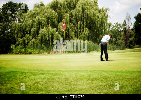 Rear view of golfer playing on grassy field - Stock Photo