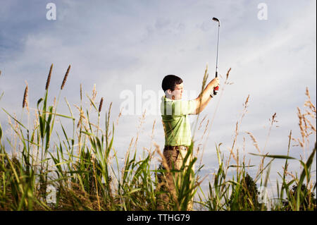 Side view of male golfer swinging golf club on field against sky - Stock Photo